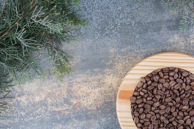 Uma placa de madeira com grãos de café sobre fundo de mármore. foto de alta qualidade