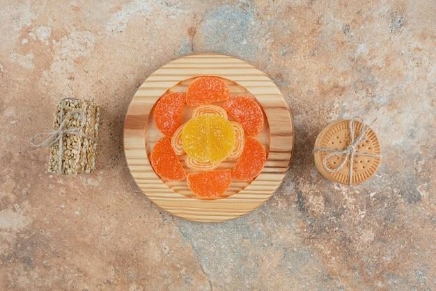 Uma placa de madeira com marmelada e biscoitos no fundo de mármore