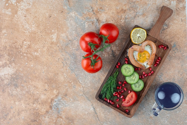 Uma placa de madeira com omelete e legumes com um copo de bebida.