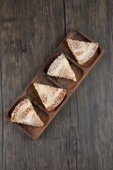 Uma placa de madeira com pedaços de um delicioso bolo sobre uma mesa de madeira.