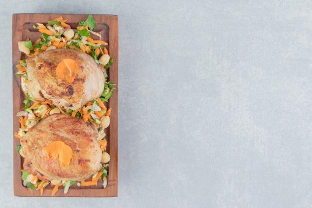 Uma placa de madeira com pernas de frango frito e salada de legumes.