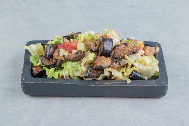 Uma placa de madeira com salada de legumes e berinjela frita.