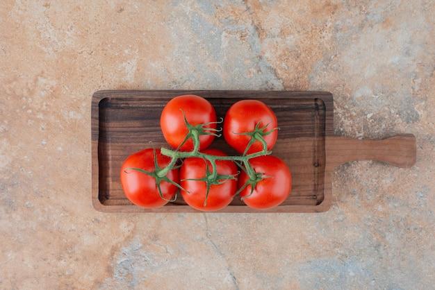Uma placa de madeira com tomates frescos em mármore
