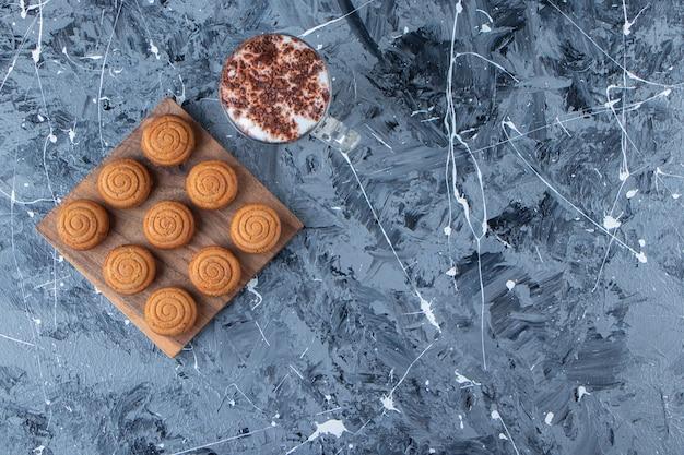 Uma placa de madeira de biscoitos doces redondos com um copo de café quente saboroso sobre um fundo de mármore.