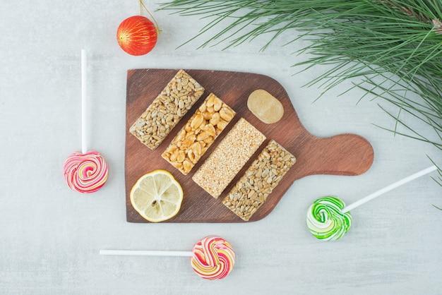 Uma placa de madeira de frágil de amendoim e uma fatia de limão. foto de alta qualidade