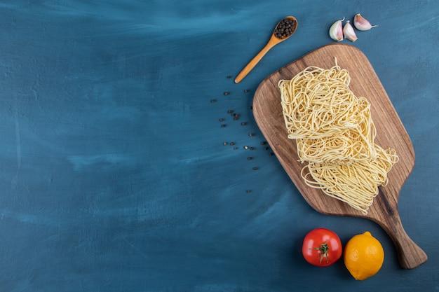 Uma placa de madeira de macarrão cru com tomate vermelho fresco e limão em um fundo azul.