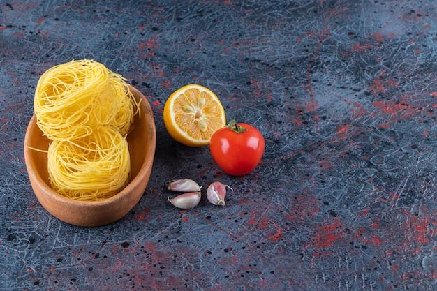 Uma placa de madeira de macarrão ninho seco cru com limão e tomate vermelho fresco em um fundo escuro.