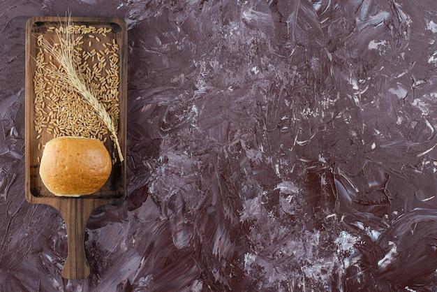 Uma placa de madeira de pão branco fresco com espiga de trigo sobre fundo claro.