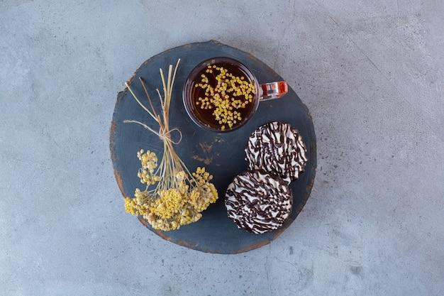 Uma placa de madeira de uma xícara de chá quente com biscoitos e flor de mimosa.