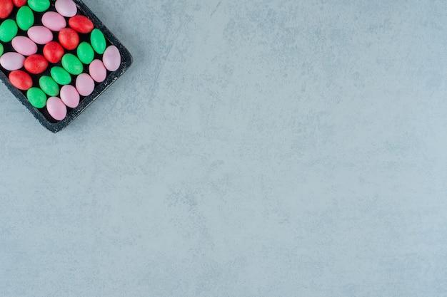 Uma placa de madeira escura cheia de doces coloridos doces redondos na superfície branca