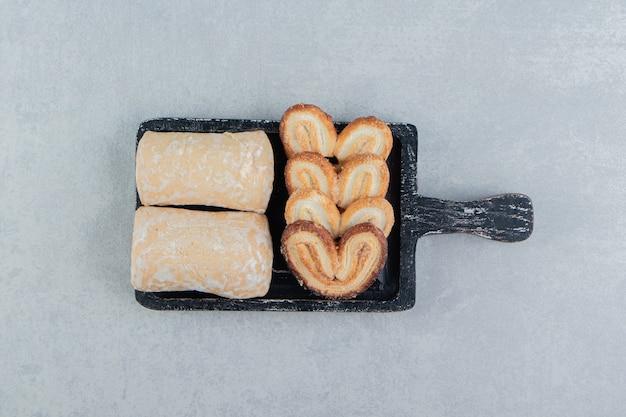 Uma placa de madeira escura com biscoitos em forma de coração doce.