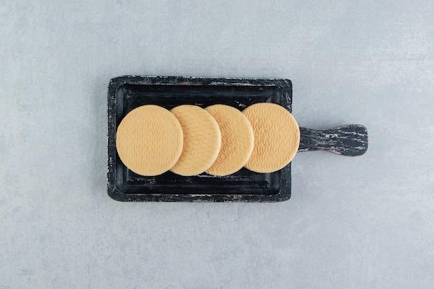 Uma placa de madeira escura com biscoitos redondos doces.