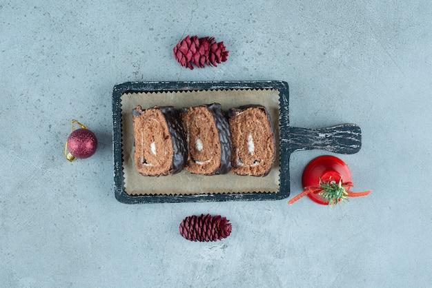 Uma placa de madeira escura com fatias de pão de ló com creme.