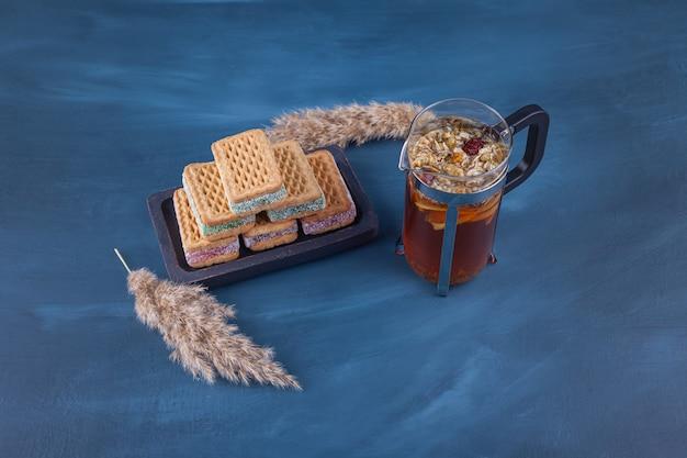 Uma placa de madeira escura com waffles doces com espigas de trigo.