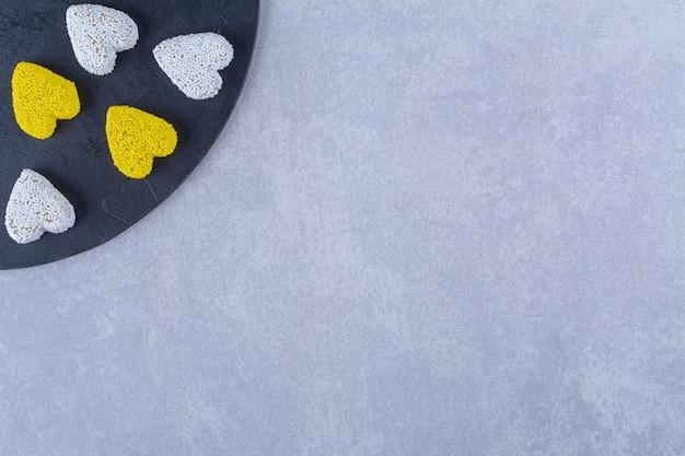 Uma placa de madeira preta cheia de balas de geleia açucaradas