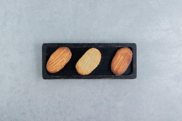 Uma placa de madeira preta cheia de biscoitos doces.