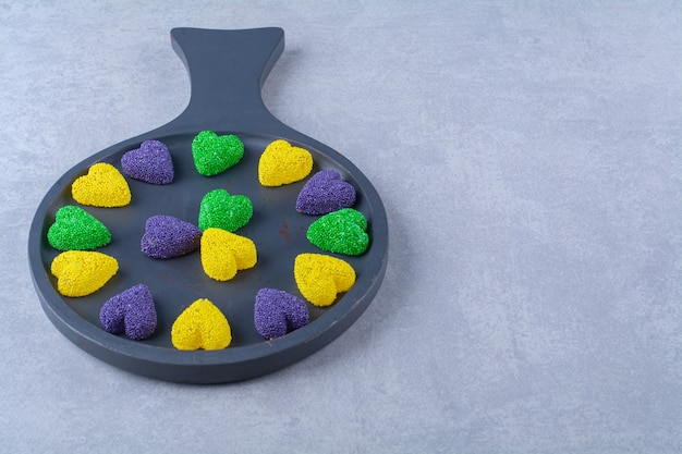Uma placa de madeira preta cheia de doces coloridos açucarados.