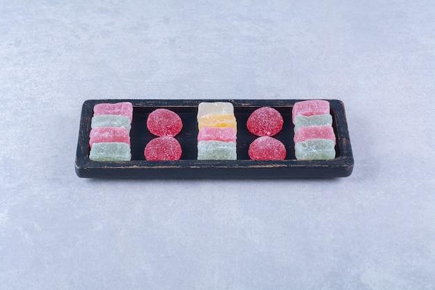 Uma placa de madeira preta cheia de doces coloridos açucarados