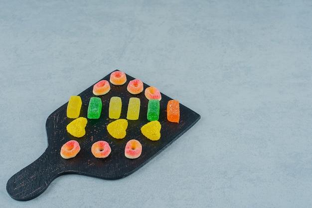 Uma placa de madeira preta cheia de doces coloridos de gelatina de frutas em uma superfície branca