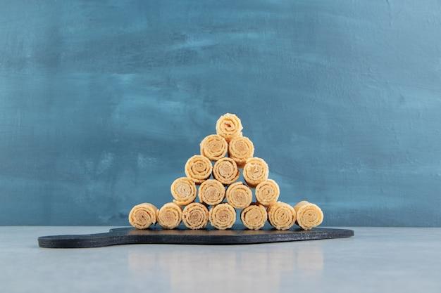 Uma placa de madeira preta cheia de rolos de waffle crocantes.