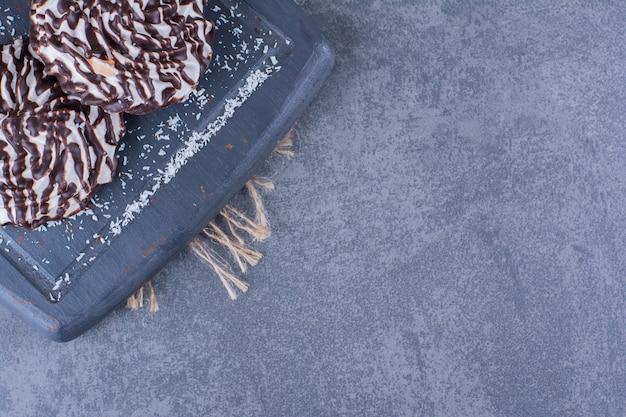 Uma placa de madeira preta de biscoitos doces em um saco.