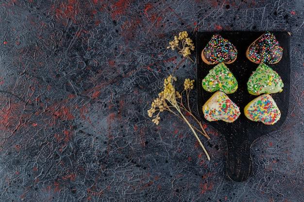 Uma placa de madeira preta de biscoitos em forma de coração com granulado com flor de mimosa.