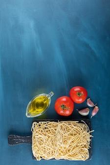 Uma placa de madeira preta de macarrão cru com dois tomates vermelhos frescos e óleo sobre uma superfície azul.