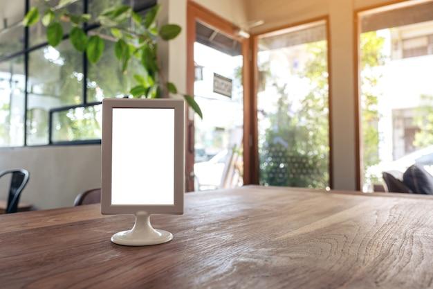 Uma placa de menu em branco na mesa de madeira de um café