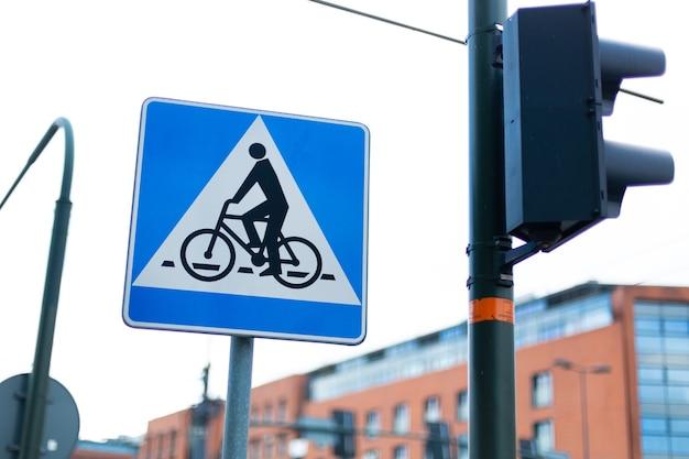 Uma placa de passagem de bicicleta ao lado de um semáforo