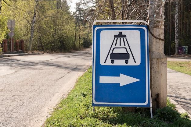 Uma placa de trânsito indicando um lava-rápido instalado em uma estrada nos subúrbios