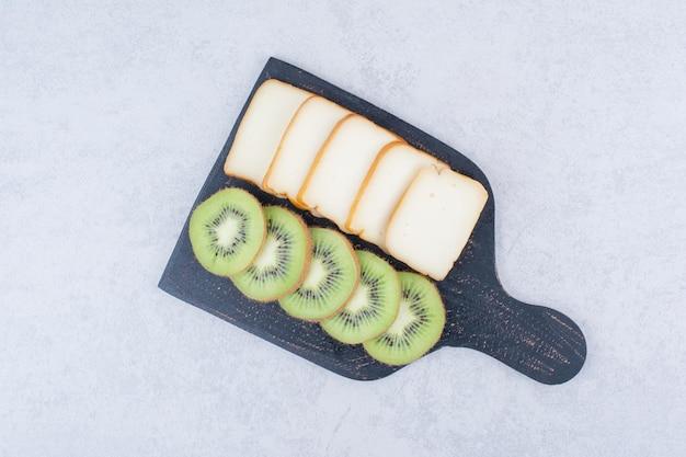 Uma placa escura com pão fatiado e kiwi fresco. foto de alta qualidade