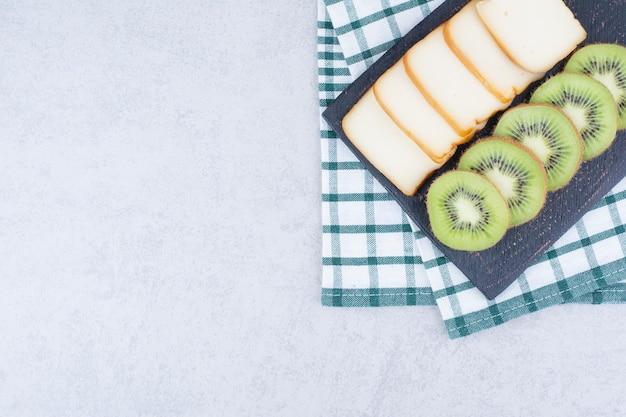 Uma placa escura com pão fatiado e kiwi fresco.