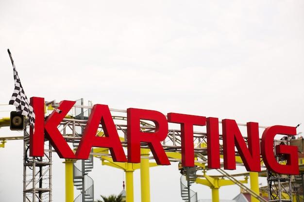 Uma placa para gocarting na estrada, a palavra karting em vermelho é volumosa