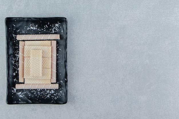 Uma placa preta cheia de rolos de waffle crocantes.