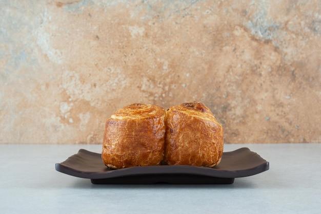 Uma placa preta com pastelaria doce deliciosa na mesa branca.