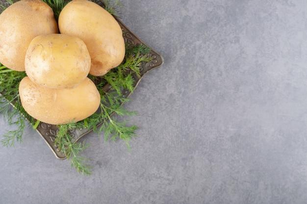 Uma placa preta de batatas cruas com endro fresco.