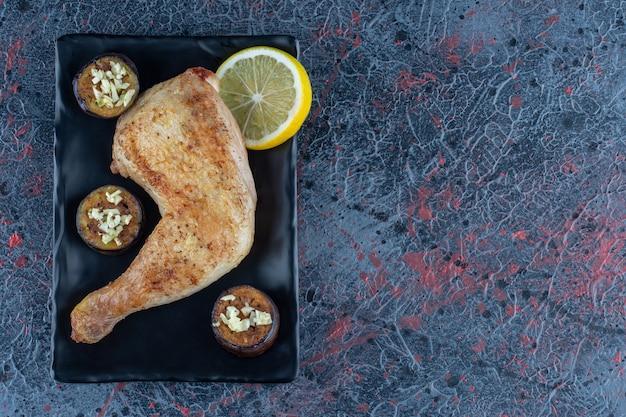 Uma placa preta de coxa de frango grelhado com berinjela frita.