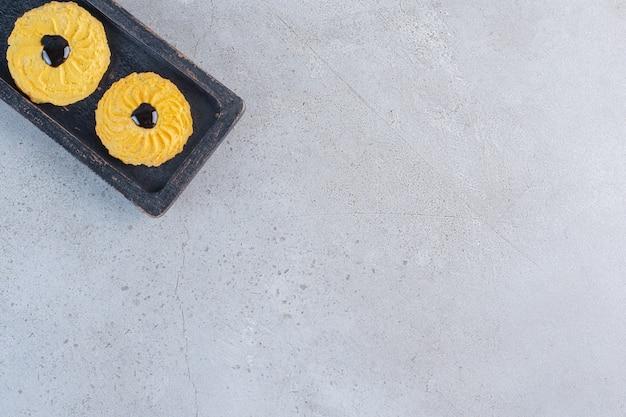Uma placa preta de deliciosos biscoitos redondos sobre fundo de pedra.