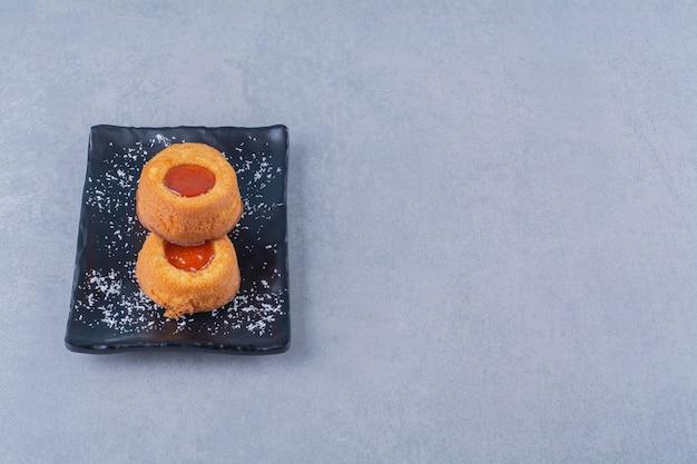 Uma placa preta de dois cupcakes doces frescos com geléia.