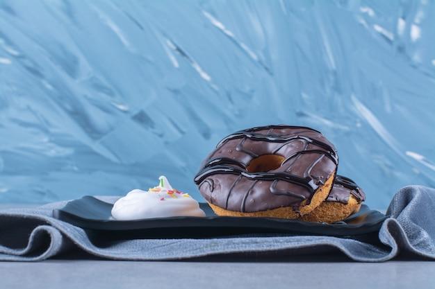 Uma placa preta de donuts de chocolate doce na toalha de mesa.