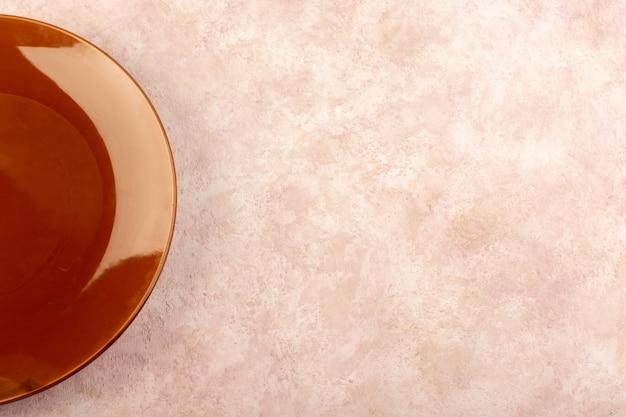 Uma placa redonda marrom de vista de cima em um copo vazio feito de uma cor de mesa de refeição isolada