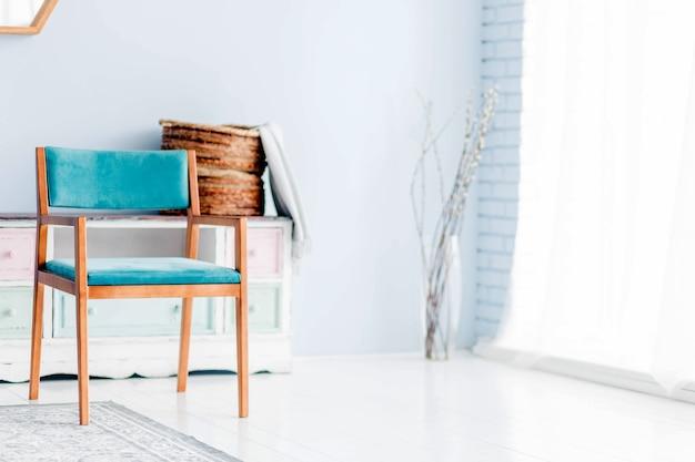 Uma poltrona azul fica em frente a uma janela com cortinas brancas. foto horizontal