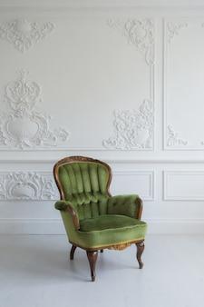 Uma poltrona clássica contra uma parede e um piso brancos. copie o espaço