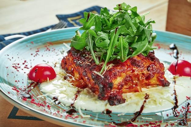 Uma porção apetitosa de lasanha caseira, apenas assada com carne e queijo, molho de natas e rúcula em um prato de cerâmica em uma mesa de madeira. configuração de mesa de restaurante
