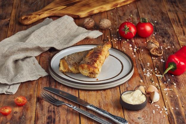 Uma porção de filé de pescada frita e maltratada, mesa de madeira com guardanapo