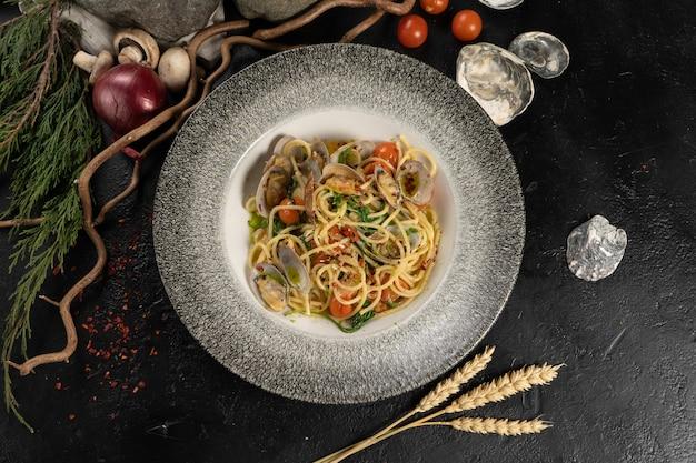 Uma porção de macarrão espaguete cozido com frutos do mar, mexilhões e vegetais