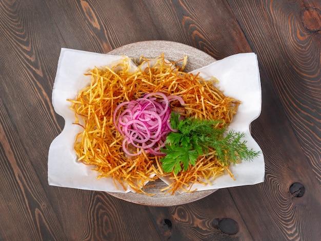 Uma porção de uma salada de batatas fritas, cebola roxa e legumes frescos em uma tigela sobre uma mesa de tábuas abandonadas vista superior