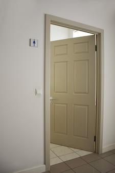 Uma porta aberta de cor clara para o banheiro feminino com uma placa na parede. o chão é revestido a ladrilhos. quadro em perspectiva