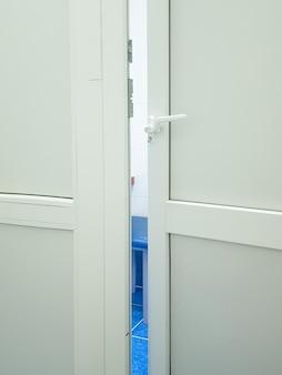 Uma porta ligeiramente aberta para um laboratório médico ou consultório médico, uma moldura vertical.