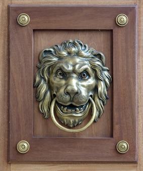 Uma porta marrom com bela maçaneta em bronze estilo retro entalhada em forma de cabeça de leão
